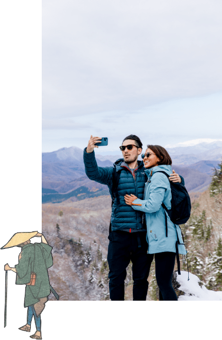 Photo: A man and woman taking selfies on a mountaintop, and a traveler watching them.